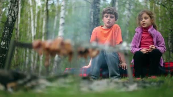 jungen und Mädchen sitzen und reden, Fleisch kochen in Glut