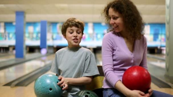 Máma a syn bowlingové koule držet v rukou a hovořit v zářivě klubu