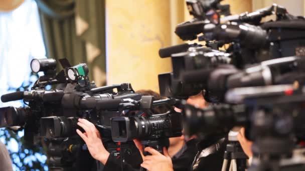 einige Videokameras mit Bedienern schließen Aufnahmepräsentation auf