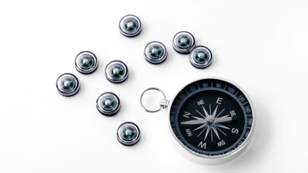 Nine small black plastic compasses and one big isolated