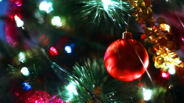 palla giocattolo di vetro riflette i raggi di luce sullalbero di Natale tra di ghirlande lampeggiante