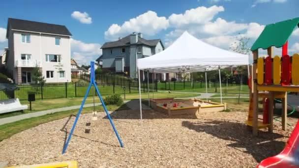 panorama dal parco giochi per bambini con collina e swing a case di campagna