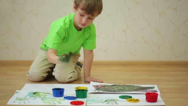 Junge zeichnet Farbe und macht Handabdrücke auf Blatt Papier
