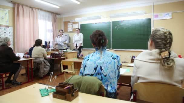 několik dospělé samice sedící na schůzce v učebně školy
