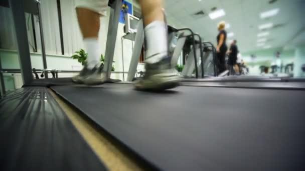 Männerfüße gehen in großer Turnhalle schnell auf Laufband