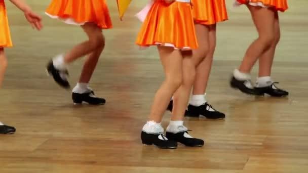 Fünf Mädchen in Schuhen mit Wasserhähnen und orangefarbenen Röcken tanzen Stepptanz
