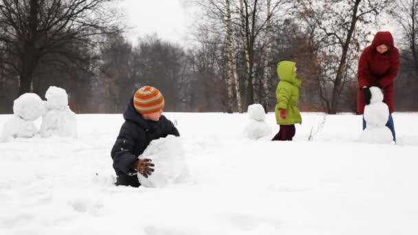 matka s dvěma dětmi sněhuláka v zimě