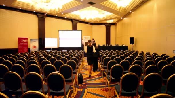 lidé chodí v prázdné konferenční sál během přestávky