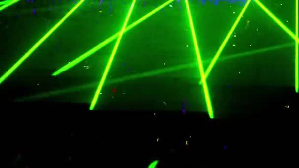 Many people at rave party, green light lazer beam lattice