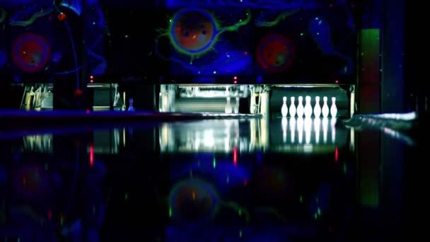 kuželky na bowling lane svítí v tmavém klubu, lidé házet míčky
