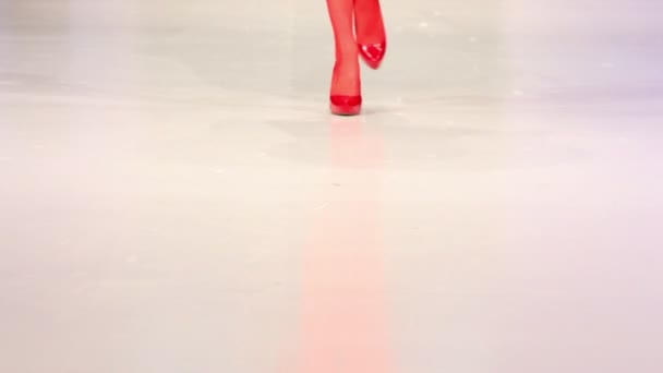 Woman walk in red shoes and red stocking by podium surface