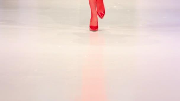 donna a piedi in scarpe rosse e rosso calza di superficie podio