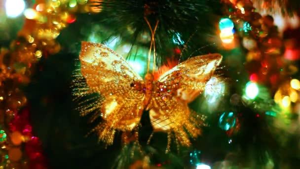 Schmetterlingsspielzeug hängt am Weihnachtsbaum zwischen blinkenden bunten Girlanden