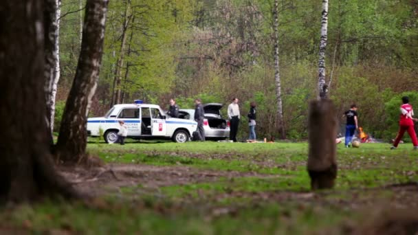 Two cops near police car speak with violators