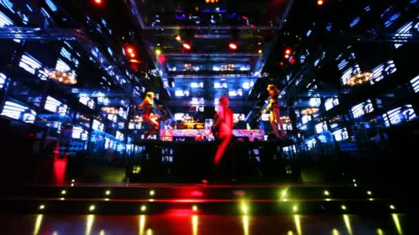 Two girls dancing on platforms in nightclub with monitors walls