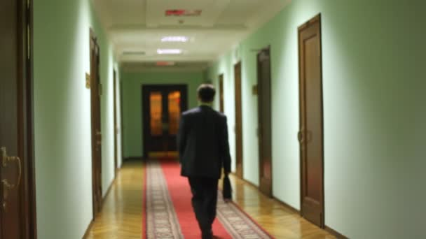 za náměstka asistent odchází po chodbě a otevírací dveře