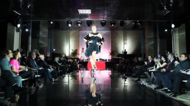 Model in dress with cape on her shoulders walks catwalk at Evening of French fashion