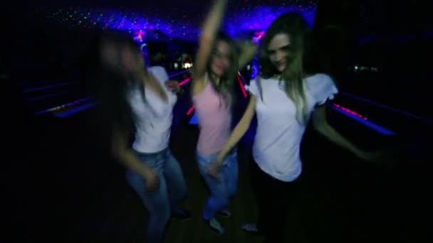 tři dívky tančí a pak fouká polibky detailní záběr na pozadí bowlingové dráhy