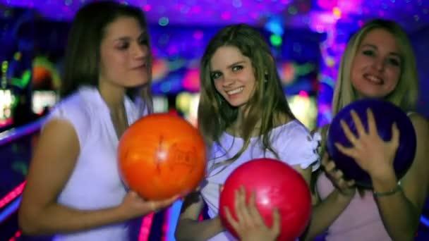 tři dívky stojí s bowlingové koule a pak hodit ji porazit kuželky