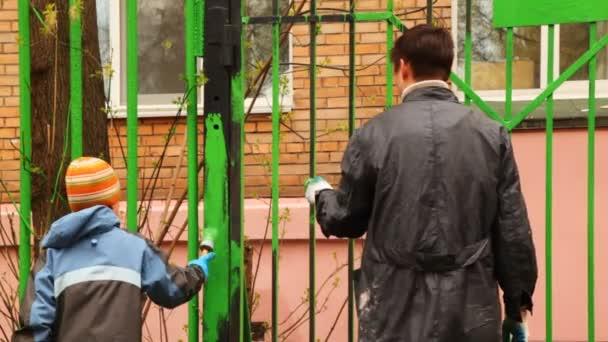chlapec a otec se štětcem v ruce pečlivě barvení plot Společenství pracovní den