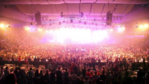 Sok rave Party rajongók, dj emelkedik a kezét a színpadon