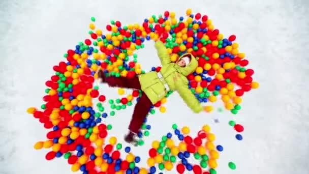 malá holčička v hromadu barevných míčků v prohlubni sníh
