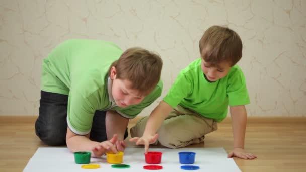 dva chlapce nakreslení barvy laky na listech papíru