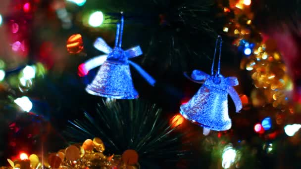 due campane giocattolo appendere sullalbero di Natale tra del lampeggiante ghirlande colorate