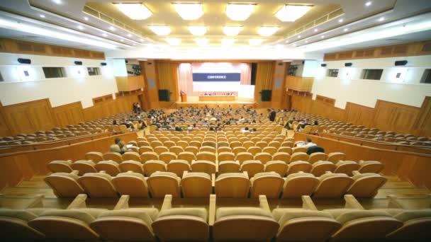 mnoho lidí sedět ve velkém sále s dřevěnými židlemi na konferenci