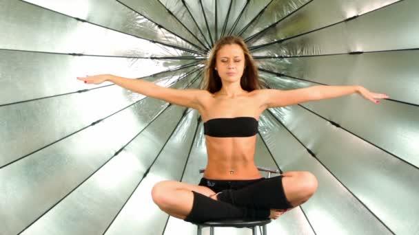 mladý model sedí s přeloženou nohy a ruce, ona medituje