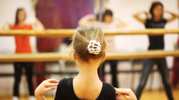 Little girl repeats movement elbows of adults dancers standing in mirror