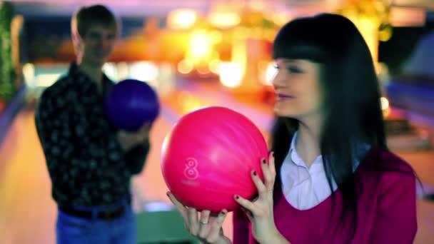 chlapec a dívka drží bowlingové koule a úsměv a pak se stávka