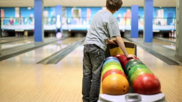 malý chlapec má jednu z bowlingové koule a vyvolá to porazit kuželky