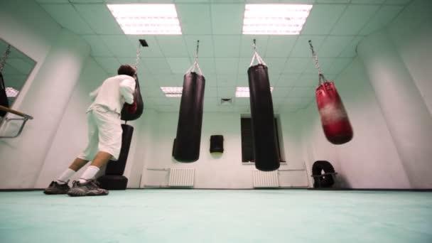 Mannen i handskar hopp och slag på små tunga slagsäck på boxning gym–  stockfilm c598cc186aa55