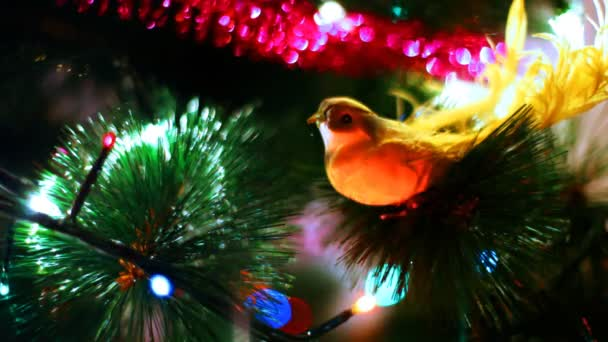 Yellow bird toy sits on Christmas tree among of blinking colored garlands