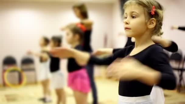 Mädchen lernen, wie man mit Ballettlehrer in Erholungszentrum tanzen