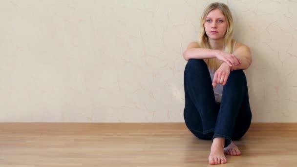 mladá dívka sedí na podlaze s zpět stisknuta proti zdi