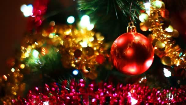 palla giocattolo rosso vetro appende su un albero di Natale tra di ghirlande lampeggiante