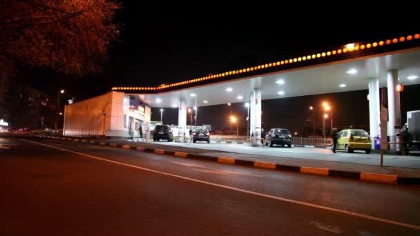 mehrere Autos füllen Treibstoff an Tankstelle in der Stadt bei Nacht