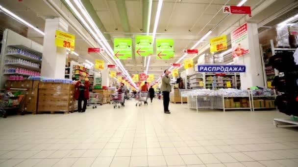 lidé chodí v hypermarketu auchan v obchodním centru trojky