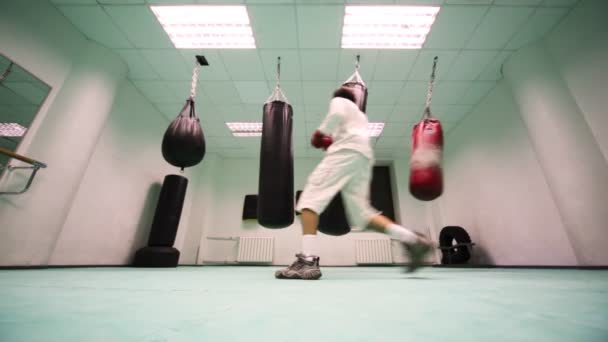 Man in gloves jumps and punches on light punching bag, then lot of hard at boxing gym