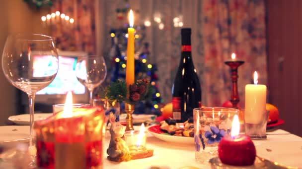 Weihnachtlich dekorierter Esstisch mit Flasche, Gläsern, Süßigkeiten, Kerzen