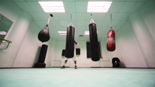 Mannen i handskar hopp och slag på två stora tunga slagsäck på boxning gym–  stockfilm 941a5e37ff0d1