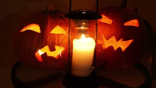 dvě dýně halloween s plameny uvnitř a stará lampa na svíčku