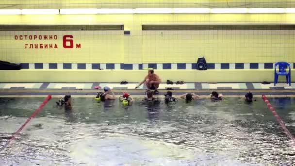 trenér učí potápěči skupiny wich plovoucí blízko okraje u bazénu