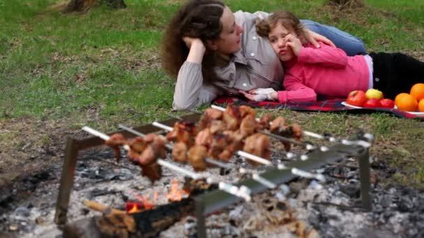 Mutter und Tochter liegen auf kariertem Gras, Teller mit Früchten liegen daneben