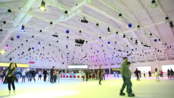 Many people skate on ice rink with colored illumination in shopping center