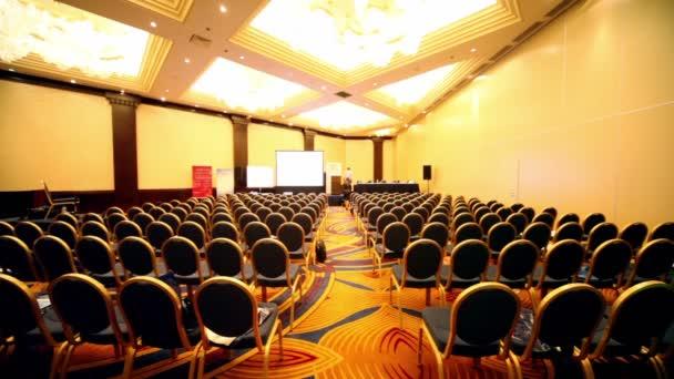 jen málo lidí chodí v prázdné konferenční sál během přestávky