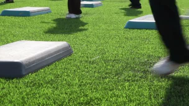 masové fitness na stadionu, pouze nohy jsou viditelné