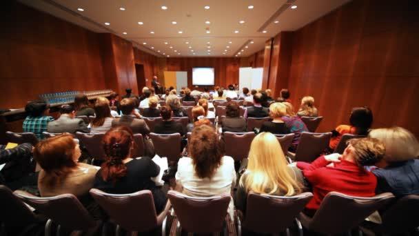 Publikum im langen kleinen Saal lauscht Vortrag des Vortragenden